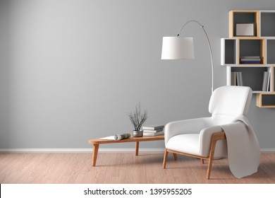 Interior of living room with cozy white leather armchair with plaid, wooden triangular coffee table, floor lamp and bookshelf on the fray wall. 3d illustration