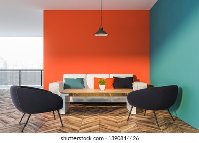 Interior of living room with orange and blue walls, wooden floor and white sofa with colorful cushions near wooden coffee table with black armchairs. 3d rendering