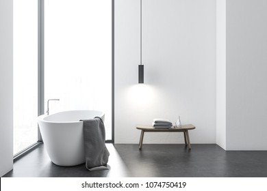 Interior of a loft bathroom with a concrete floor, a large windows with a cityscape, a white bathtub and table with towels. 3d rendering