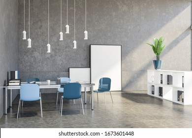 Interior of loft design studio office with concrete walls and floor, big table with blue chairs, white bookshelves with folders and vertical mock up poster standing on the floor. 3d rendering