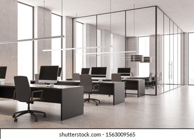 Interior of loft open space office with concrete white walls, concrete floor, rows of gray computer tables and glass wall conference room. 3d rendering
