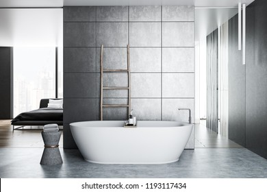 Interior of luxury bathroom with gray tile walls, concrete floor, white bathtub and wooden ladder near the wall. Master bedroom in the background. 3d rendering