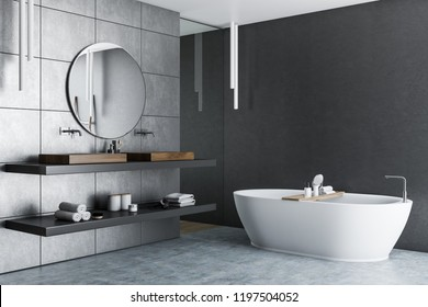 Interior of luxury bathroom with gray tile walls, concrete floor, white bathtub and double sink with a round mirror hanging above it. 3d rendering