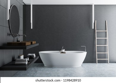 Interior of luxury bathroom with gray tile walls, concrete floor, white bathtub and double sink with a round mirror hanging above it. Wooden ladder in the corner. 3d rendering