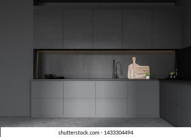 Interior of minimalistic kitchen with dark gray walls, concrete floor, gray countertops with built in sink and black cupboards with dishes and cutting boards. 3d rendering