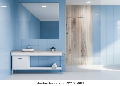Interior of modern bathroom with blue walls, white floor, glass and wooden shower and white sink standing on white and wooden countertop with big square mirror hanging above it. 3d rendering