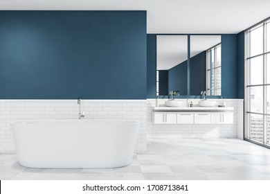 Interior of modern bathroom with blue and white brick walls, tiled floor, comfortable white double sink with two vertical mirrors and cozy bathtub. Window with blurry cityscape. 3d rendering