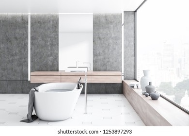 Interior of modern bathroom with concrete walls, tiled floor, panoramic window, white bathtub and white sink with vertical mirror above it. 3d rendering