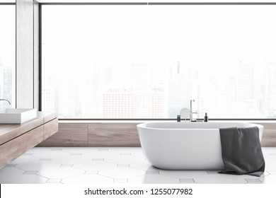 Interior of modern bathroom with concrete walls, tiled floor, panoramic window with cityscape, white bathtub and white sink standing on wooden counter. 3d rendering