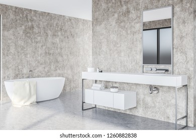 Interior of modern bathroom with concrete walls and floor, white bathtub and white sink with vertical mirror above it. 3d rendering