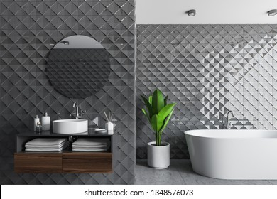 Interior of modern bathroom with gray tile walls, concrete floor, white bathtub and round wink with mirror above it standing on wooden shelf. 3d rendering