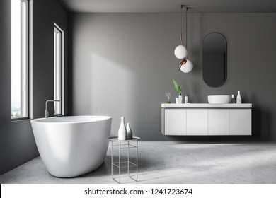 Interior of modern bathroom with gray walls, concrete floor, white bathtub standing near loft window and white sink on gray countertop. 3d rendering