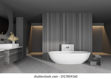 Interior of modern bathroom with gray walls, concrete floor, white bathtub and double sink with round mirror on dark gray counter. 3d rendering