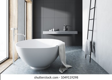 Interior of a modern bathroom with gray and white walls, a concrete floor and a white bathtub near the window. 3d rendering mock up