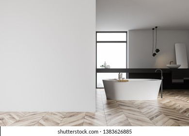 Interior of modern bathroom with white and gray walls, wooden floor, white bathtub standing under window and white sink with mirror on gray shelf. Mock up wall to the left. 3d rendering