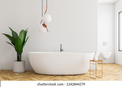 Interior of modern bathroom with white walls, wooden floor, white bathtub standing next to chair with shampoo and potted plant. 3d rendering