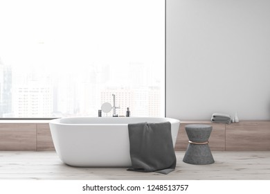 Interior of modern bathroom with white walls, wooden floor, panoramic window with cityscape, white bathtub and gray chair. 3d rendering