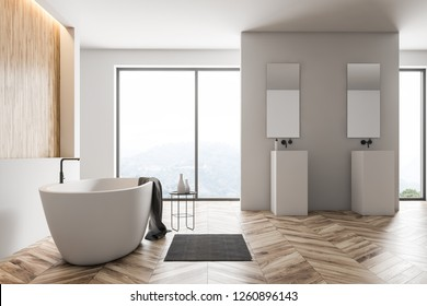 Interior of modern bathroom with white and wooden walls, wooden floor, large windows with mountain view, white bathtub and two square sinks with mirrors above them. 3d rendering