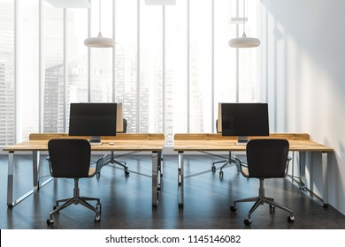 Interior of a modern consulting company office with panoramic windows with a city view, a concrete floor and wooden computer desks standing in a row. 3d rendering mock up