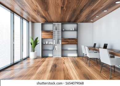 Interior of modern coworking style office with white walls, wooden floor and ceiling, long wooden table with white chairs and laptops and bookcase. Window with blurry cityscape. 3d rendering