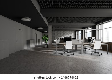Interior of modern industrial style office with gray geometric pattern walls, concrete floor, columns, gray doors and rows of gray computer tables with white chairs. 3d rendering