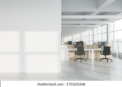 Interior of modern Industrial style open space office with white walls, concrete floor, rows of computer tables and panoramic windows with blurry cityscape. Mock up wall. 3d rendering