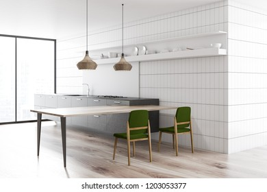 Interior of modern kitchen with white tile walls, gray countertops, long wooden table with green chairs and stylish ceiling lamps. 3d rendering