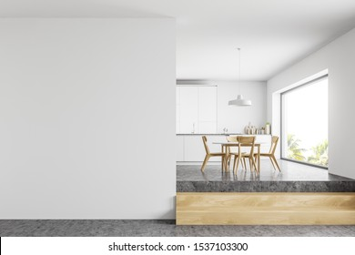 Interior of modern kitchen with white walls, concrete floor, white countertops, round table with wooden chairs and mock up wall to the left. 3d rendering