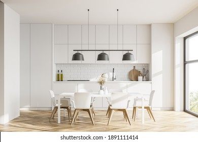 Interior of modern kitchen with white walls, wooden floor, dining table and cupboards. 3d rendering