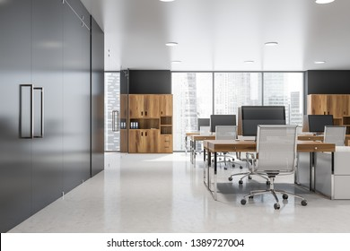Interior of modern office with gray walls, rows of wooden computer desks with metal chairs and wooden bookcases with folders. 3d rendering