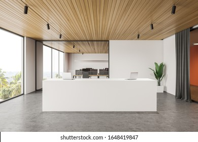 Interior of modern office hall with white and orange walls, concrete floor, comfortable white reception desk with two laptops on it and open space area in background. 3d rendering