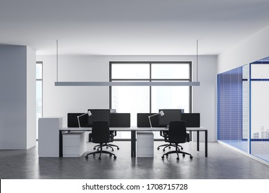 Interior of modern open space office with white and bright blue walls, concrete floor, comfortable workplaces with white and black computer tables and window with blurry cityscape. 3d rendering