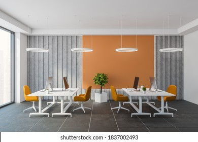 Interior of modern open space office with orange and gray walls, tiled floor and big computer tables with orange chairs. 3d rendering