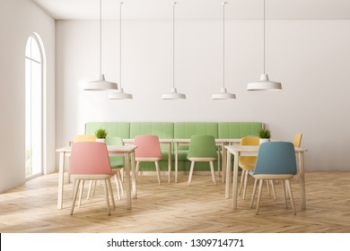 Interior of modern restaurant with white walls, wooden floor, arched window, long green sofa and square wooden tables with pastel colored chairs. 3d rendering