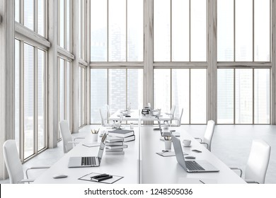 Interior of open space office with tall windows, concrete floor and rows of white tables with laptops and books on them. 3d rendering