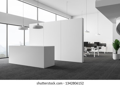 Interior of open space office with white walls, carpeted floor, rows of computer desks with gray chairs and minimalistic reception table with laptop on it. 3d rendering