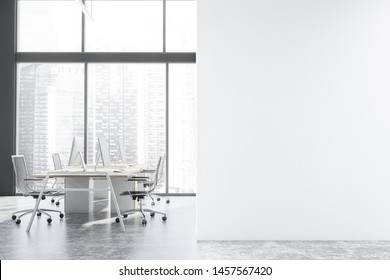 Interior of panoramic open space office with gray walls, concrete floor, large windows with cityscape and rows of white and wooden computer tables. Mock up wall to the right. 3d rendering