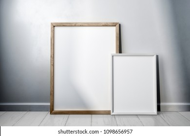 Interior poster mock up with two different-sized vertical empty wooden and white  frames standing on white wooden floor,  in room with white wall. 3d rendering