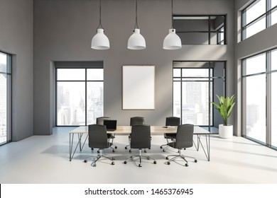 Interior of spacious office conference room with grey walls, white floor, large windows, wooden meeting table with black chairs, laptop and vertical mock up poster frame. 3d rendering