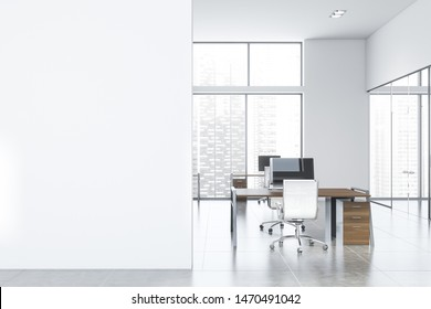 Interior of spacious open space office with white walls, tiled floor and rows of dark wooden computer desks. Mock up wall on the left. 3d rendering