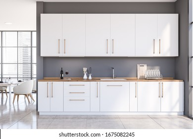 Interior of spacious panoramic kitchen with grey walls, tiled floor, white countertops and cupboards and dining table with armchairs in background. 3d rendering