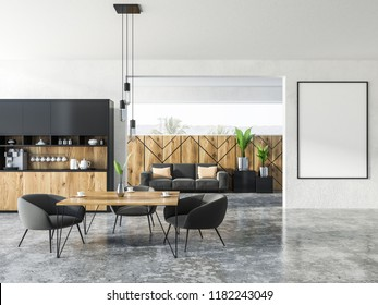 Interior of studio apartment with kitchen corner, a square table with gray armchairs and sofa with cushions. Mock up vertical poster fram on the wall 3d rendering