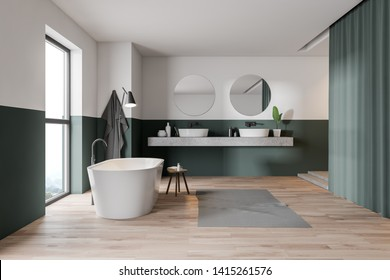 Interior of stylish bathroom with green and white walls, wooden floor, white bathtub, double sink and curtains. 3d rendering