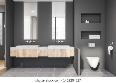 Interior of stylish bathroom with grey walls, tiled floor, stone and wooden double sink with vertical mirrors above it and toilet in the corner. 3d rendering