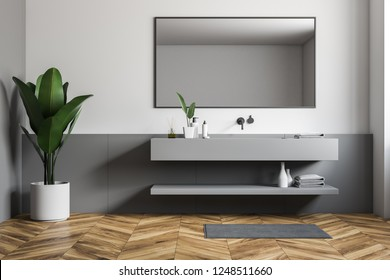 Interior of stylish bathroom with white and gray walls, wooden floor and long gray sink with horizontal mirror hanging above it. 3d rendering