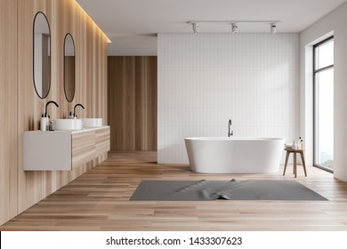 Interior of stylish bathroom with white tile and wooden walls, wooden floor, white bathtub with carpet near window and double sink with mirrors on wooden countertop. 3d rendering