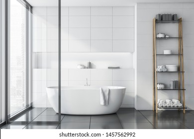 Interior of stylish bathroom with white tile walls, gray tile floor, comfortable white bathtub and shelves with towels and creams. 3d rendering