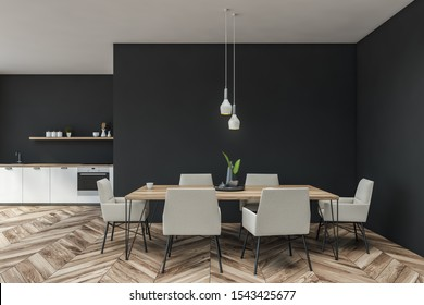 Interior of stylish kitchen with dark gray walls, wooden floor, white countertops with built in sink and oven and wooden shelf with dishes. Long dining table with white chairs. 3d rendering