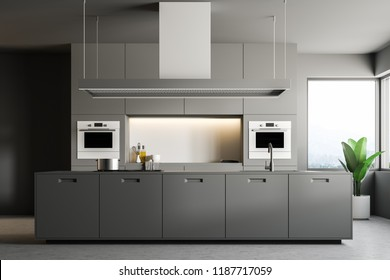 Interior of stylish kitchen with gray walls, concrete floor, gray countertops with built in appliances, and an island. 3d rendering copy space