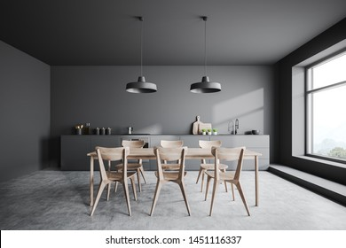 Interior of stylish kitchen with gray walls, concrete floor, gray countertops with built in sink and cooker and long wooden table with chairs. 3d rendering